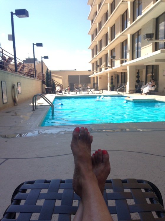 View of woman's feet in foreground, sun-lit hotel swimming pool in background
