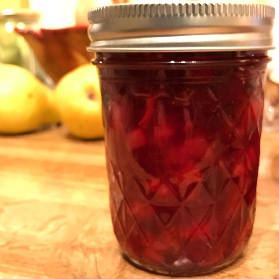 Spiced cranberry sauce in jelly jar in foreeground, pears, fruit bowl in background
